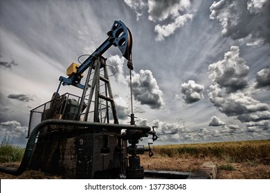 Oil pump, industrial machine for petroleum in the sunset background