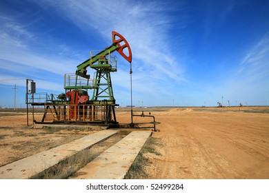 An oil pump jack on blue sky.