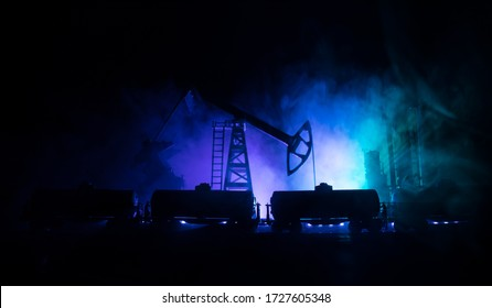 Oil pump and oil refining factory at night with fog and backlight. Energy industrial concept. Night industrial railway with oil tank wagons. Selective focus. Artwork decoration.