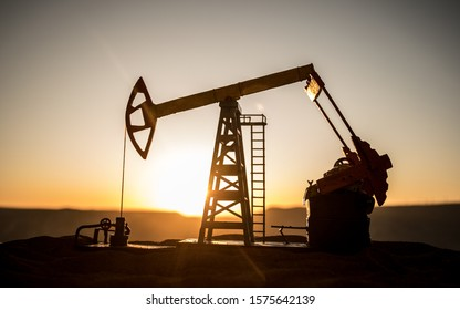 Oil pump and oil refining factory at sunset. Energy industrial concept. Selective focus. Creative artwork decoration.