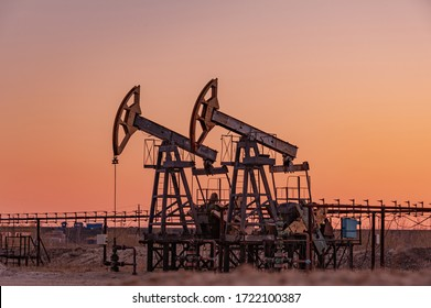 Oil pump rig. Oil and gas production. Oilfield site. Pump Jack are running. Drilling derricks for fossil fuels output and crude oil production. War on oil prices. Global coronavirus COVID 19 crisis.