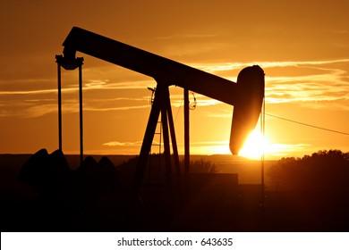 oil pump silhouette against a bright orange sky