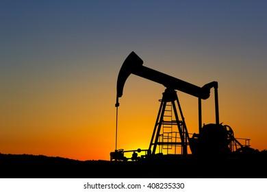Oil pump silhouette over sunset sky