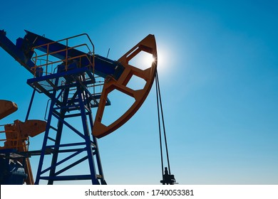 Oil pump are working in the blue sky background.  World Oil Industry. Western region of Kazakhstan. A oil pump is the overground drive for a reciprocating piston pump in an oil well.