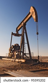 An oil pumper at sunset on the plains of West Texas, USA