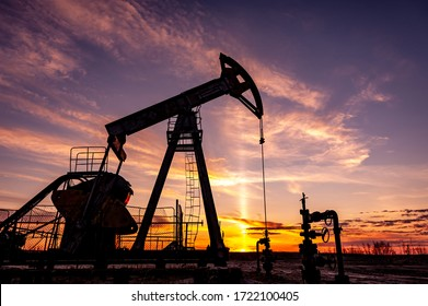 Oil Pumpjack against a sunset sky on background. industrial equipment. Rocking machines for power genertion. Extraction of oil. War on oil prices. Global coronavirus COVID 19 crisis.