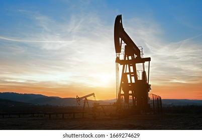 Oil pumps. Oil industry equipment. Oil rocking at sunset
