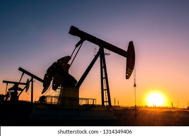 Oil pumps are running in the sunset at the oil field. The outline of the pumping unit.