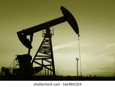Oil pumps at work, silhouetted against the setting sun