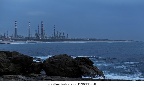 Oil refinery by the sea at dusk
