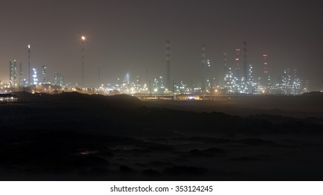 Oil refinery by the sea at night, near a rocky beach. Long exposure.