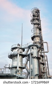 Oil refinery chemical plant vertical bottom view with copy space over evening sky background.