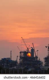 Oil refinery construction in silhouette
