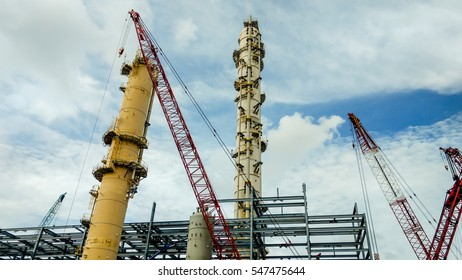 Oil refinery construction site; Distillation columns and mega crane with beautiful sky.