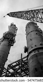 Oil refinery construction site; Distillation columns and mega crane with beautiful sky. Shoot in black and white close up shot.