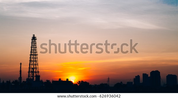Oil refinery factory and logistic over sunrise Bangkok Thailand, with silhouette, Industrial zone, The equipment of oil refining, industrial pipelines of an oil-refinery plant, copy space.