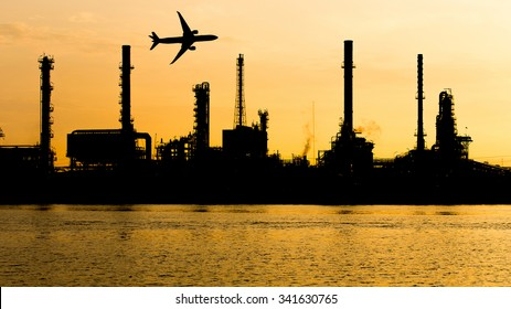 Oil refinery industry plant silhouette with airplane over in the morning.