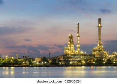 Oil refinery light after sunset view, river front, industrial landscape background