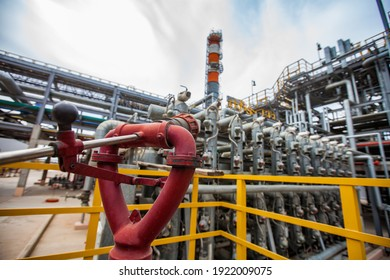 Oil refinery plant safety technologies. Fire extinguisher system. Distillation tower and pipelines on background.