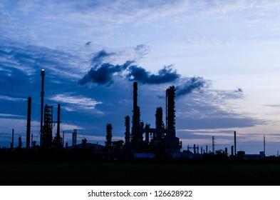 Oil refinery plant silhouette at twilight dark blue sky.