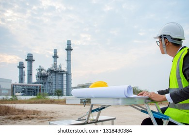 Oil refinery plant at sunrise with sky background. Engineer discussing a new project with large industry background.