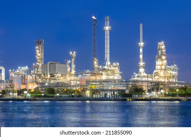 Oil refinery reflected on river at twilight.