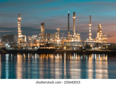Oil refinery reflected on river, vintage color tone.
