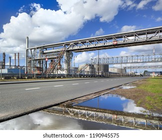 Oil refinery with scaffolds and crossing pipelines reflected in a pond against a blue sky with dramatic clouds, Port of Antwerp, Belgium