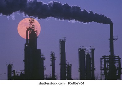 An oil refinery silhouetted against the eerie red of a full moon