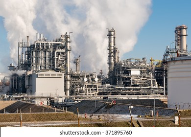 oil refinery with smoking chimneys against blue sky