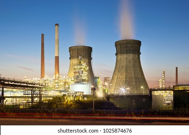 An oil refinery with two cooling towers and blue night sky.
