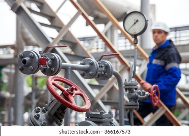 The oil refinery, the worker in a difokus checks the indication of a monometer and examines gates and cranes.