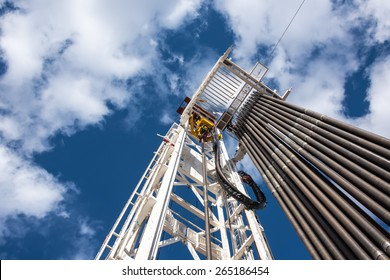 Oil rig derrick in oilfield against the bright blue sky