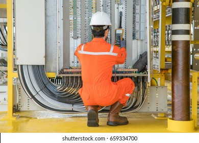 Oil rig electrician and instrument worker wearing safety personal protective equipment measuring voltage by using digital multi meter at offshore oil and gas remote platform