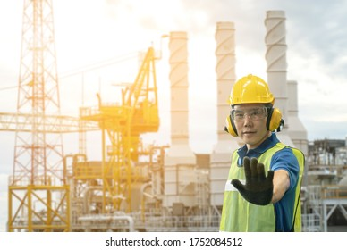 oil rig offshore and Asian worker staff engineer lift his hand prohibit signal