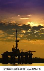 Oil rig platform in colorful sunrise.