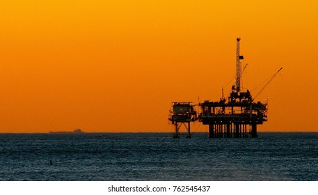 Oil rig silhouetted against the orange sky of the sunsetting behind the Pacifico Ocean horizon, Huntington Beach, California.