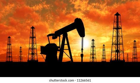 Oil rig silhouettes over orange sky