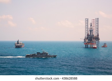 Oil rig and oil tanker ship with patrol vessel sailing pass in the gulf