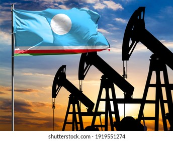 Oil rigs against the backdrop of the colorful sky and a flagpole with the flag of Sakha Republic. The concept of oil production, minerals, development of new deposits.