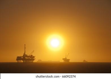 Oil rigs, ship and sunset in the ocean. Huntington Beach, California.