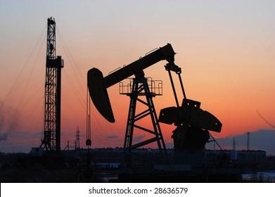 oil rigs silhouette over orange sky