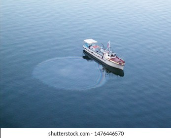 oil slick on water and water pollution and oil spill from a boat