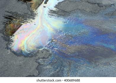 Oil spill on asphalt road background or texture