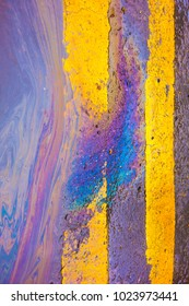 Oil Spill Rainbow Liquid on Yellow Lines on Road