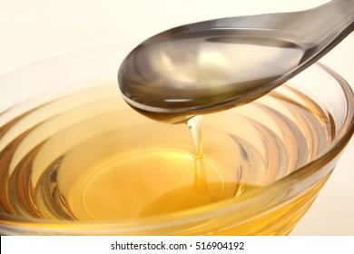 Oil with spoon in white background/ Oil