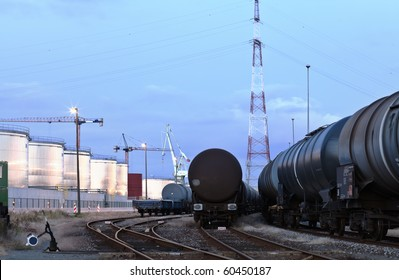Oil tank cars standing on rail tracks in industrial area; twilight scene