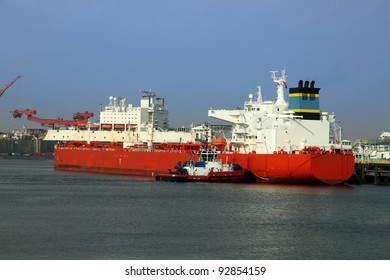 Oil tanker being moored with the aid of a tugboat in the harbor of Rotterdam