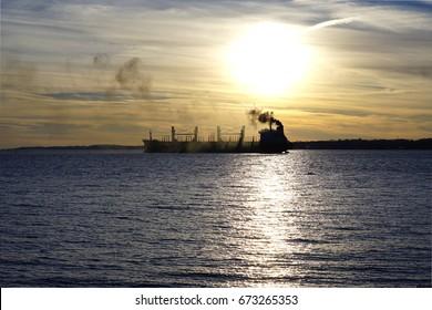Oil tanker discharging black smoke at dusk