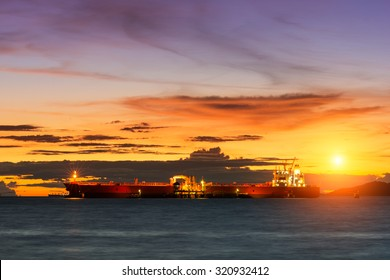 Oil Tanker loading oil in the sea with sunset